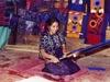 Une femme tissant un tapis ou un habit